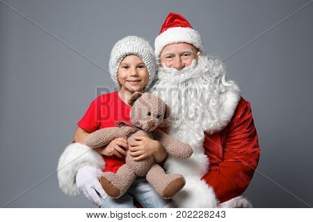Cute little boy with teddy bear sitting on Santa's lap against color background