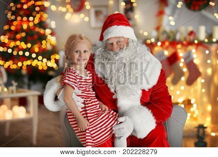Little girl sitting on Santa's lap in room with beautiful Christmas decorations