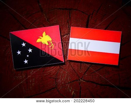 Papua New Guinea Flag With Austrian Flag On A Tree Stump Isolated