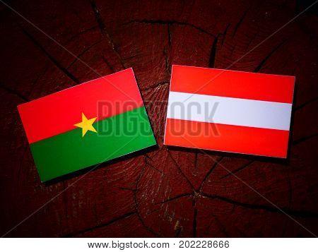 Burkina Faso Flag With Austrian Flag On A Tree Stump Isolated