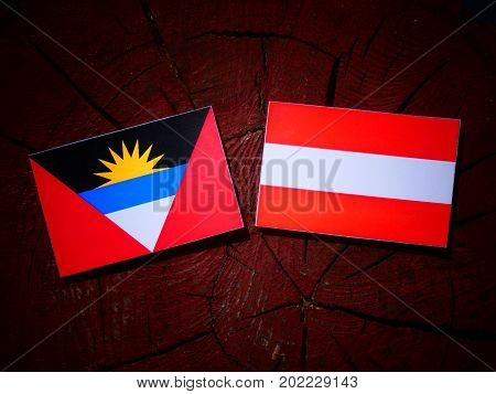 Antigua And Barbuda Flag With Austrian Flag On A Tree Stump Isolated