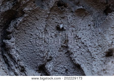 Black volcanic cosmetic clay in a bowl. cosmetic clay texture close up. solution cosmetic clay abstract background
