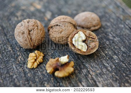 Whole and cracked walnuts at old wooden plank. Still life with selective focus.