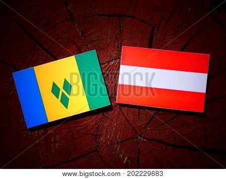 Saint Vincent And The Grenadines Flag With Austrian Flag On A Tree Stump Isolated