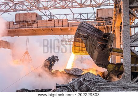 Pouring the red-hot melt by truck transporter with ladle. Metallurgical work in heavy industry.