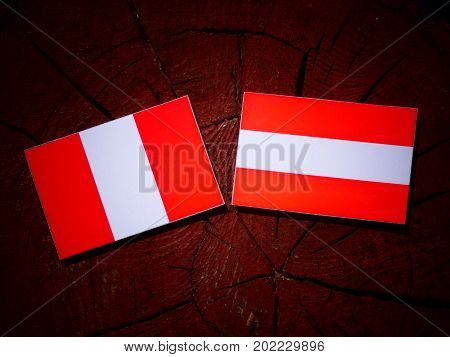 Peruvian Flag With Austrian Flag On A Tree Stump Isolated