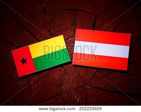 Guinea Bissau Flag With Austrian Flag On A Tree Stump Isolated