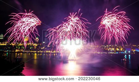 Pink and white fireworks over the Saint-Lawrence River with a part of Quebec city in the background. Quebec, Canada.
