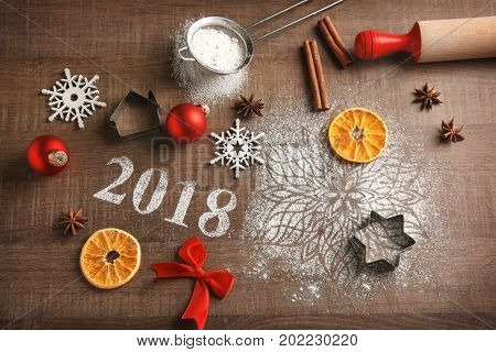Cookie cutters, Christmas decor and 2018 made of flour on wooden table
