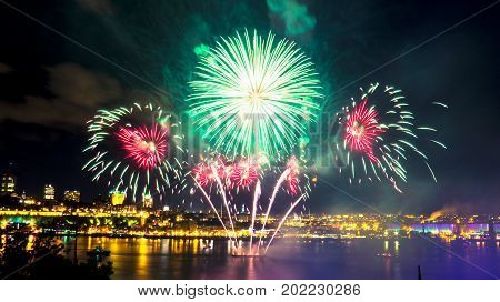 Green and red fireworks over the Saint-Lawrence River with a part of Quebec city in the background. Quebec, Canada.