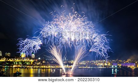 Blue fireworks over the Saint-Lawrence River with a part of Quebec city in the background. Quebec, Canada.