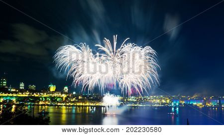 White fireworks over the Saint-Lawrence River with a part of Quebec city in the background. Quebec, Canada.