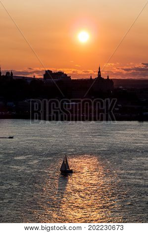 Vertical orange sunset over Quebec City with a boat sailing on the Saint-Lawrence River, Canada.