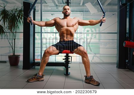 Young man flexing arm muscles on the arm press machine on a blurred light gym background. A shirtless man with perfect torso exercising and building muscles. Workout, training, fitness concept.