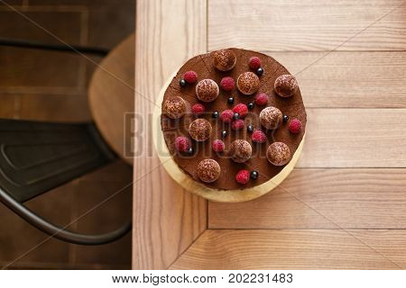 A view from above of a delicious chocolate cake with a creamy layer on a light brown wooden background. A baked round cake with ripe raspberries and black currant on a top. Sweet snacks. Copy space.