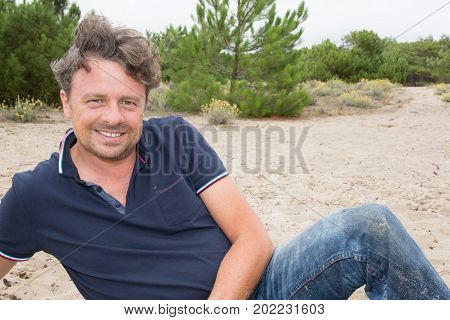 A Handsome Fit Forties Man Is Sitting On Sand In Beautiful Beach