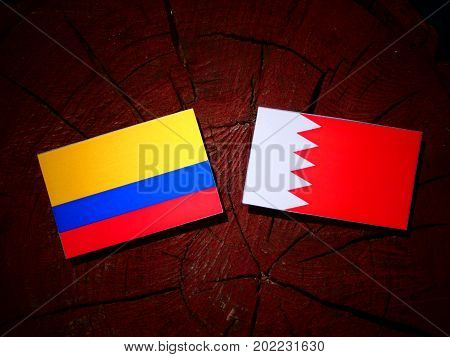 Colombian Flag With Bahraini Flag On A Tree Stump Isolated