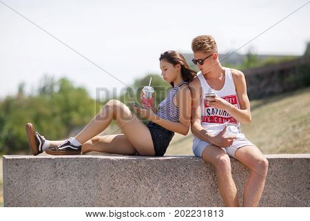 A modern couple sitting on a natural background. A youth playing on a smartphone outdoors. A teenage girl and guy drinking a pink beverage and looking in a phone on a street. Dependence on gadgets.