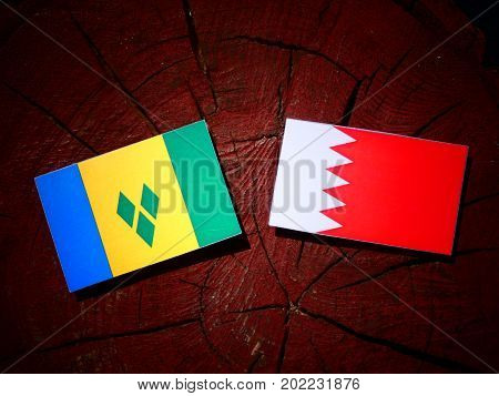 Saint Vincent And The Grenadines Flag With Bahraini Flag On A Tree Stump Isolated