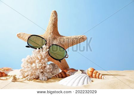 Starfish with sunglasses, shells and coral on sand against color background. Summer vacation concept