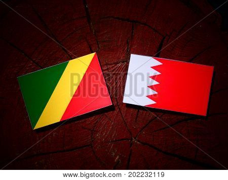 Republic Of The Congo Flag With Bahraini Flag On A Tree Stump Isolated