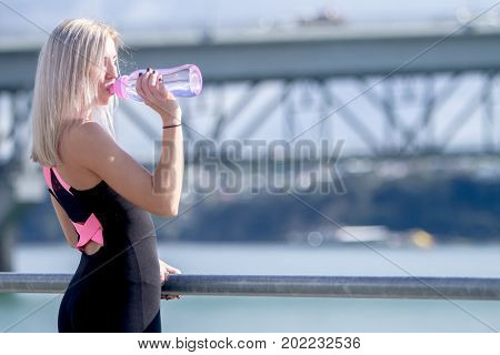 outdoor portrait of young happy blonde girl doing sport in the city, urban background