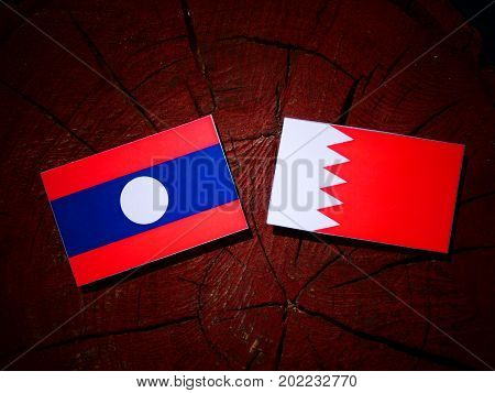 Laos Flag With Bahraini Flag On A Tree Stump Isolated