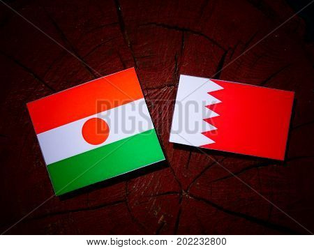 Niger Flag With Bahraini Flag On A Tree Stump Isolated