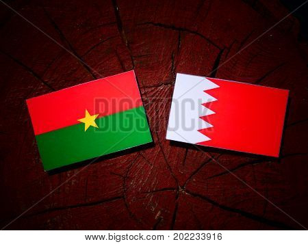 Burkina Faso Flag With Bahraini Flag On A Tree Stump Isolated