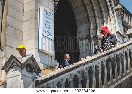 Tourists Come Out Of The Basilica Of Immaculate Design Down A Stone Staircase