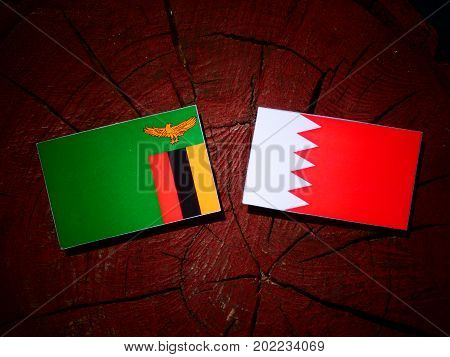 Zambia Flag With Bahraini Flag On A Tree Stump Isolated