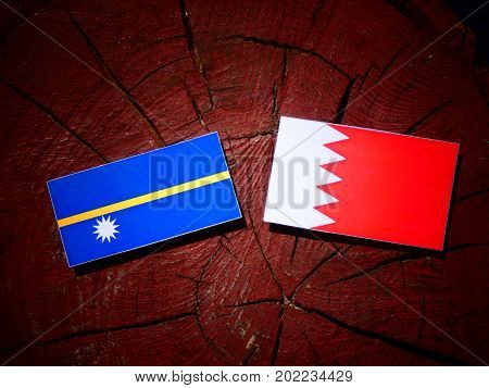 Nauru Flag With Bahraini Flag On A Tree Stump Isolated