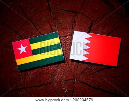 Togolese Flag With Bahraini Flag On A Tree Stump Isolated