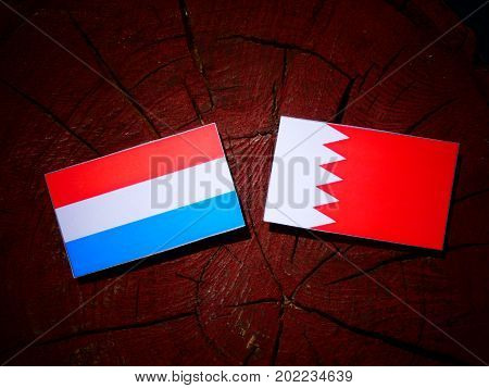 Luxembourg Flag With Bahraini Flag On A Tree Stump Isolated