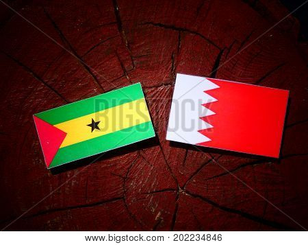Sao Tome And Principe Flag With Bahraini Flag On A Tree Stump Isolated