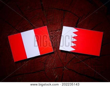 Peruvian Flag With Bahraini Flag On A Tree Stump Isolated