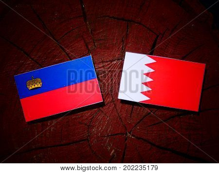 Liechtenstein Flag With Bahraini Flag On A Tree Stump Isolated