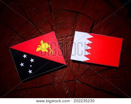 Papua New Guinea Flag With Bahraini Flag On A Tree Stump Isolated