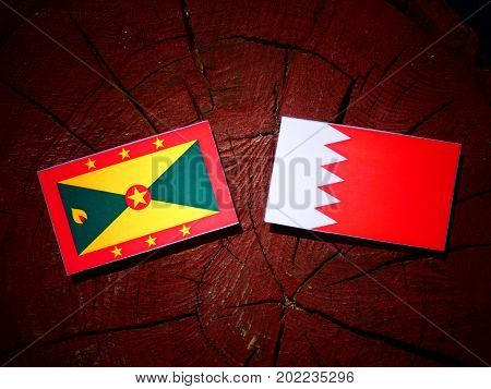 Grenada Flag With Bahraini Flag On A Tree Stump Isolated
