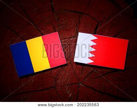 Romanian Flag With Bahraini Flag On A Tree Stump Isolated