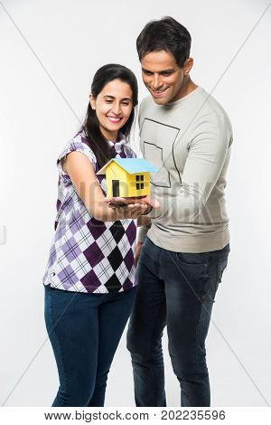 stock photo of Indian smart and cheerful / happy couple holding 3D paper house model and keys, standing isolated over white background, asian couple and real estate concept