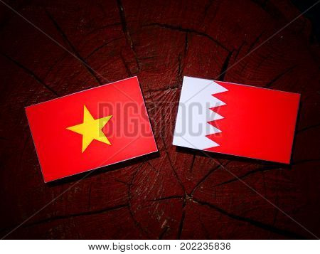 Vietnamese Flag With Bahraini Flag On A Tree Stump Isolated