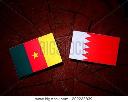 Cameroon Flag With Bahraini Flag On A Tree Stump Isolated