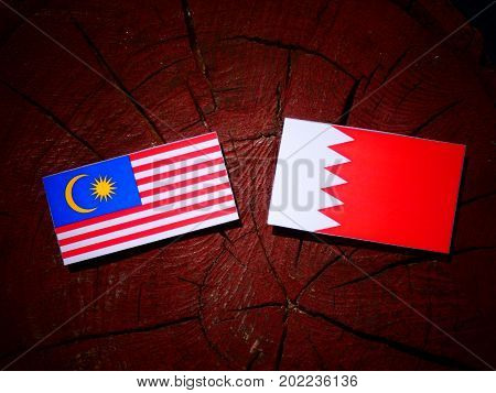 Malaysia Flag With Bahraini Flag On A Tree Stump Isolated