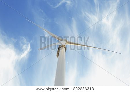 A view from the bottom of huge, tall, white electric windmill on a bright blue sky background. Ecological rotating wind turbine. Sustainable electric power and modern technology. Copy space.