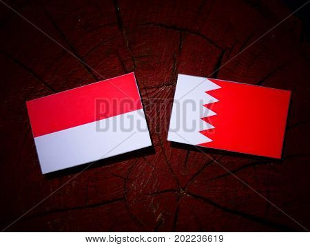 Indonesian Flag With Bahraini Flag On A Tree Stump Isolated
