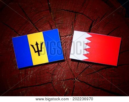 Barbados Flag With Bahraini Flag On A Tree Stump Isolated