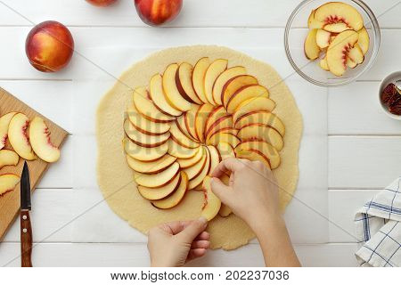 Step By Step Recipe Galette Or Pie With Nectarines. Female Hands Lay Out Slices Of Nectarine On The