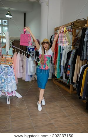 A full-length portrait of a smiling young woman in a clothing store on a blurred background. A satisfied female holding her stylish purchases in raised hands. Shopping, consumerism concept. Copy space