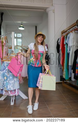 A full-length portrait of a happy young girl with colorful packets standing on a blurred background. A satisfied female holding her stylish purchases in a clothing store. Copy space. Shopping concept.